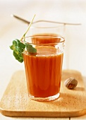 Two glasses of tomato juice with nutmeg and basil