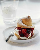 Profiterole filled with whipped cream and red berry compote