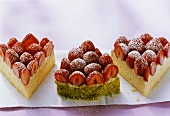 Three pieces of strawberry cake with lime cream and pistachios