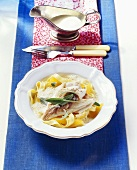 Oven-baked sea bream on ribbon pasta with orange sauce