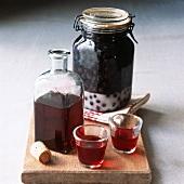 Sloe gin in carafe, glasses and preserving jar