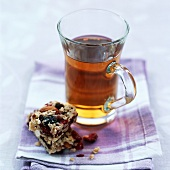 A glass of herbal tea with a muesli bar