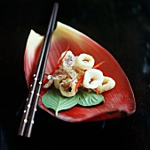 Deep-fried squid with fried basil on banana flower petal