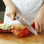Breaking open the claws of a lobster with the back of a knife