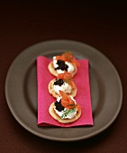 Small blinis topped with creamed horseradish, smoked salmon and caviar