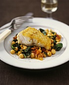 Fried hake on a bed of chickpeas and vegetables
