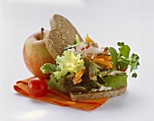 Wholemeal bread with a mixed leaf salad, vegetables and an apple
