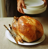 A whole roast turkey with carving knife and fork