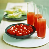 Three glasses of tomato juice with fresh tomatoes