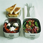 Two lunch boxes with grilled vegetables and feta