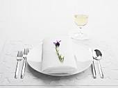 A place setting with a white napkin and a sprig of lavender