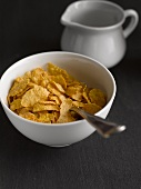 Cornflakes in a bowl in front of a jug of milk