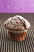 A chocolate muffin with icing sugar