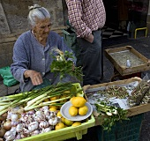 An old woman selling vegetables at a market in Jerez de la Frontera, Spain