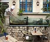 A chef at the restaurant Les Chandelles Gourmandes catching fish from the pond (Larcay, France)