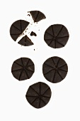 Five chocolate biscuits on a white surface