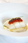 Cod on a bed of potato and olive cream with peppers and peanuts