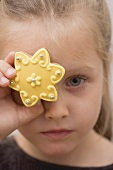 A little girl holding holding a biscuit in front of her eye