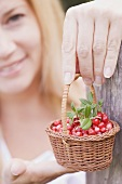 A woman holding a little basket of lingon berries