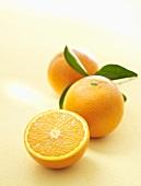 Orangen, ganz und halbiert, mit Blättern