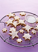 Cinnamon stars with icing sugar on a wire rack