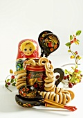 Bubliki (Russian bread rings) in a pot with a Matryoshka, wooden spoons and cranberries
