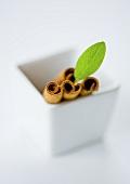Cinnamon sticks and a sage leaf in a ceramic bowl