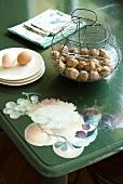 Nüsse im Drahtkorb und Eier auf Unterteller auf bemaltem Tisch