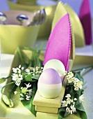 Osterdeko mit bunten Eierwärmern und Eiern