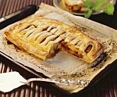 Apple strudel on baking tray, a piece taken