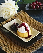 Small sponge cake with icing and cherry compote