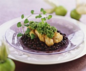Cod fillet with green salsa on black beans