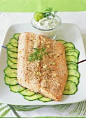 Fried salmon on cucumber slices with dill sauce
