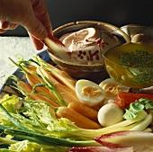 Hand holding radicchio leaf over dip on a vegetable platter