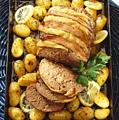 Bacon-wrapped meatloaf with potatoes on a baking tray