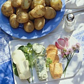 Rolls of seasoned butter & plate of potatoes cooked in skins