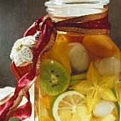 Rumtopf with exotic fruit in glass jar with gift ribbon
