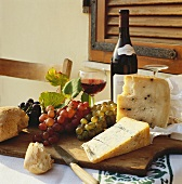 Still life with cheese, bread, wine and grapes