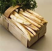 White asparagus and fresh herbs in woodchip basket