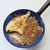 Plaice with bacon in a frying pan