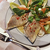 Fillet of pike with red peppercorns on salad