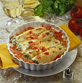 Filled cannelloni with tomatoes in a gratin dish