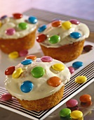 Muffins with white chocolate icing & coloured chocolate beans