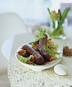 Home-made lamb sausages on warm bean salad