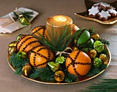 Oranges and limes studded with cloves, fir sprigs & candle