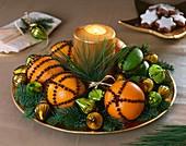 Gespickte Orangen und Limetten, Tannenzweige und Kerze