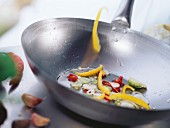 Slice of pepper falling into wok with vegetables & sesame oil