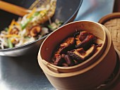Steamed shiitake in bamboo basket, stir-fried vegetables behind
