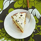 A piece of cheesecake with raisin cream topping