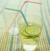 Limeade in a glass with a straw